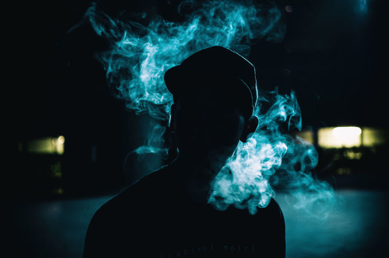 Close-Up Of Man Smoking Cigarette At Night