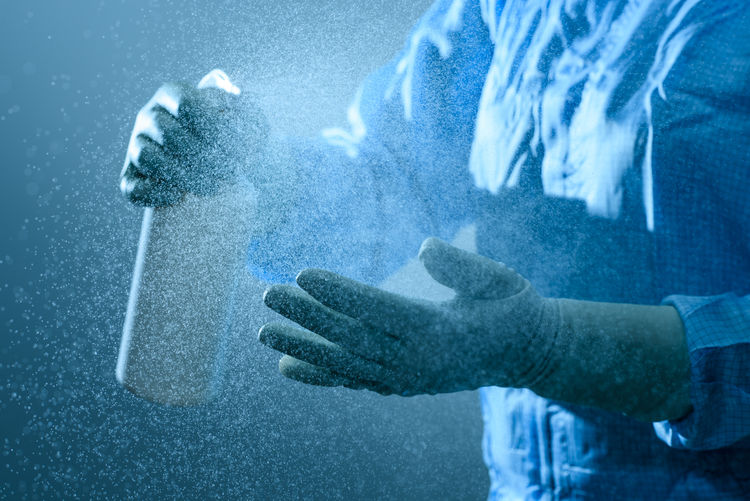 Midsection Of Person Spraying Antibacterial On Hands
