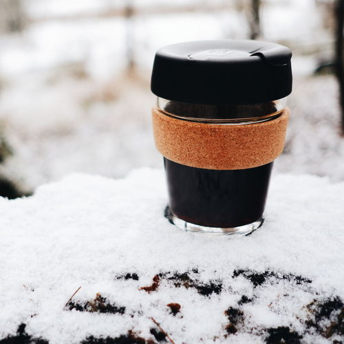 Close-up of coffee cup on snow covered field