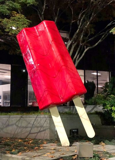 Red flag hanging on sidewalk in city