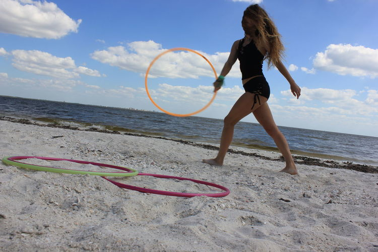 Full length of young woman playing with plastic hoop at beach against cloudy sky