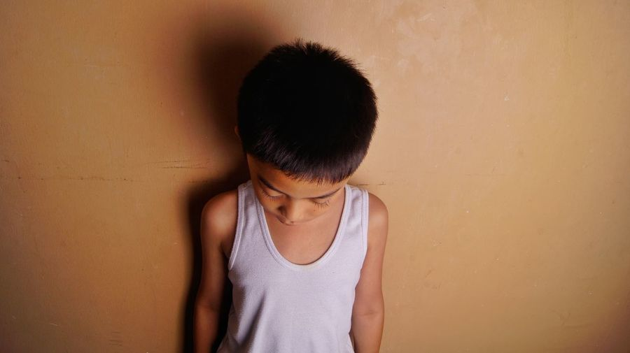 Boy standing against wall at home