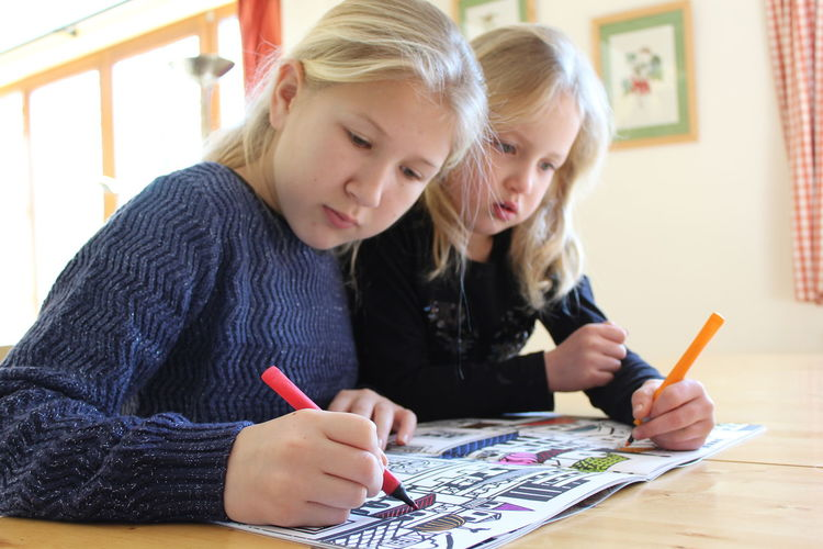 PORTRAIT OF Two Blonde Girls Coloring With Markers