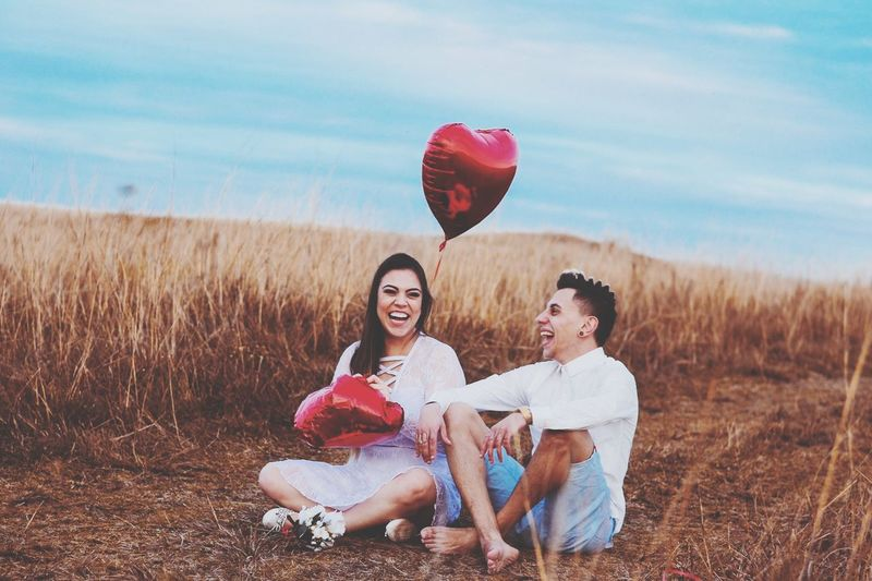 Happy Couple With Heart Shape Balloon Sitting On Field Against Sky