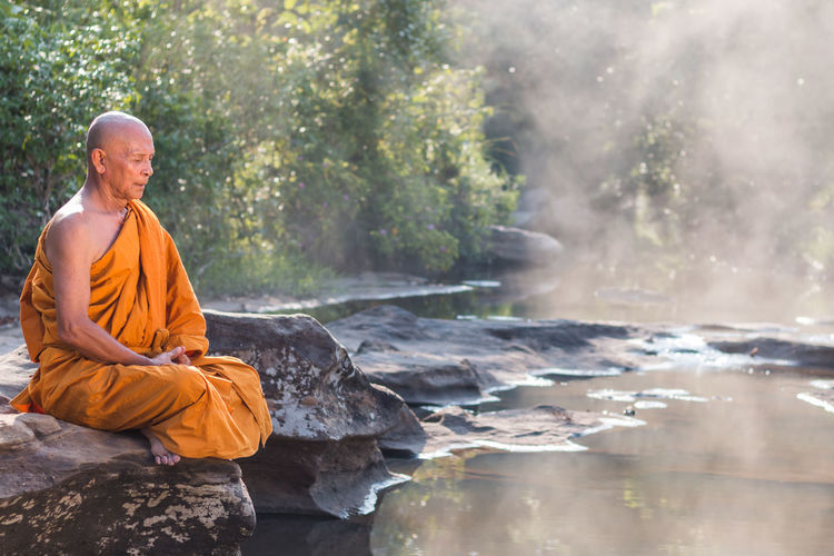 Senior Buddhist Monk By The Water