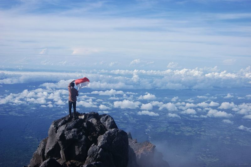 Man standing on rock by mountains against sky
