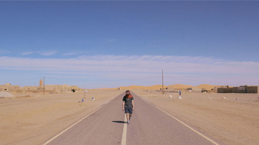 Man walking on road against sky
