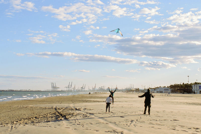 People flying kite at beach against sky