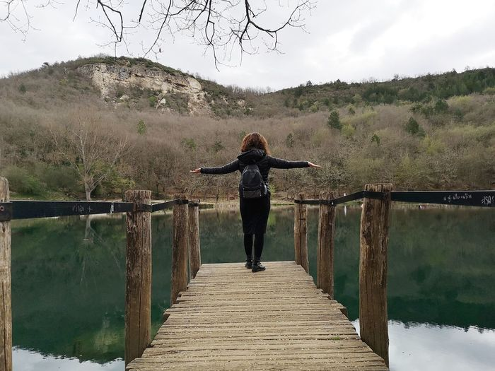 One Person Rear View Water Arms Outstretched Real People Tree Full Length Leisure Activity Railing Human Arm Standing Nature Lifestyles Wood - Material Sky Women Tranquility Plant Limb Outdoors Bridge - Man Made Structure Footbridge Lake Sinizzo