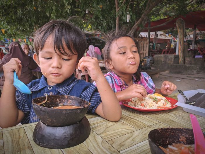 Boy and girl eating food on table at restaurant