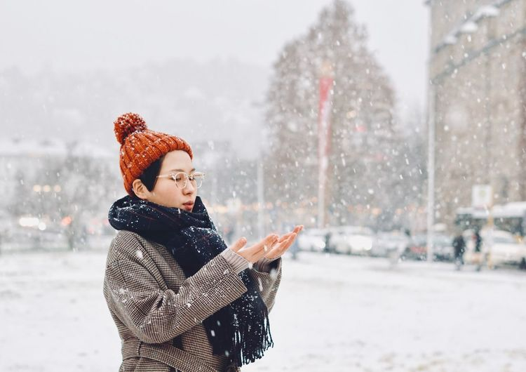 Woman Standing In City During Snowfall