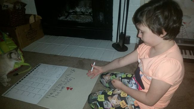 Thelilian writing a thank you card to a student for a bunch of Pokemon cards.