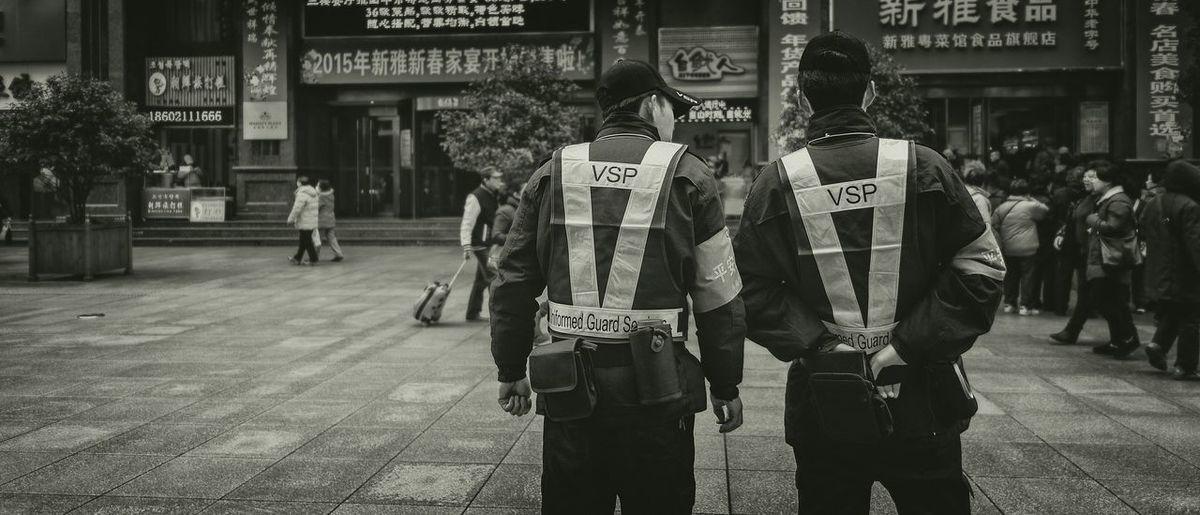 Rear view policemen looking at people standing street in city
