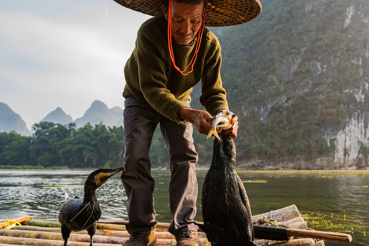 Man wearing hat standing on raft with bird