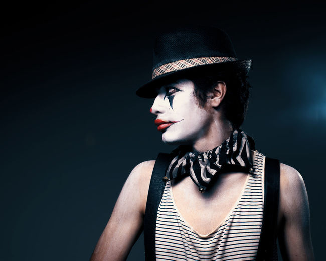 Black Background Clothing Clown Contemplation Fashion Hat Headshot Indoors  Looking Away One Person People Portrait Studio Shot Young Adult