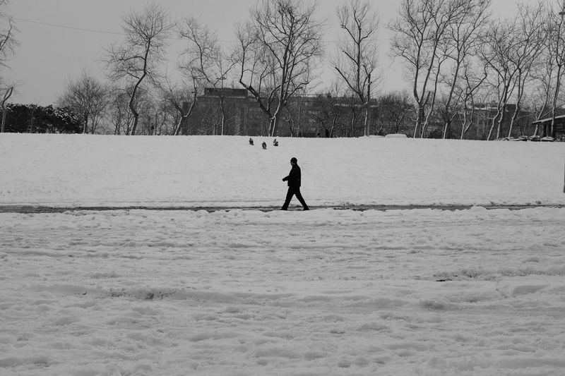 Side View Of Man Walking On Snow Covered Landscape