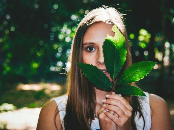 Close-up portrait of young woman holding leaves in front of face