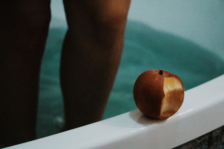 Close-up of apple against woman standing in bathtub