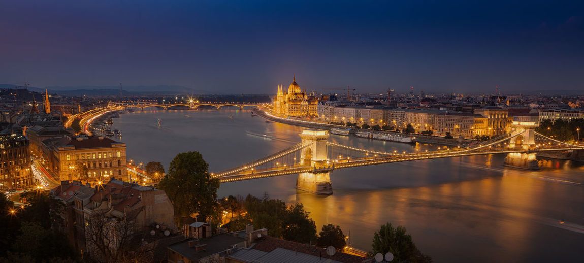 Looking down to the Danube river with parliament building and chain bridge in Budapest, Hungary Budapest Hungary Panorama Architecture Bridge Bridge - Man Made Structure Building Exterior Built Structure Chain Bridge Chain Bridge Budapest City Cityscape Illuminated Parkliament Building River Sky Tourism Transportation Travel Travel Destinations Water