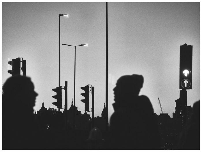 Silhouette people against illuminated sky at night