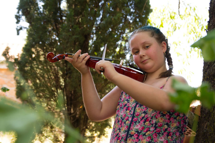 Brunette teenager with braids in her hair playing guitar. children playing instruments in nature.