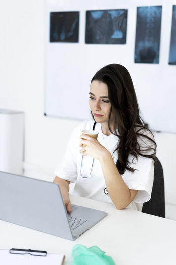 Young woman using phone on table