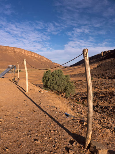 Wooden post with clothesline in the desert Sahara in Morocco. In the background is a solar panel. Wooden Post Solar Panel Morocco Arid Climate Boundary Sand Tranquility Nature Environment Landscape Barrier Climate No People Non-urban Scene Desert Sunlight Dunes Cloud - Sky Sky Clothesline Sahara Tranquil Scene Bush Shrub