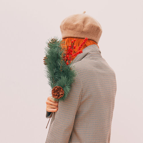 Rear view of woman holding umbrella against white background