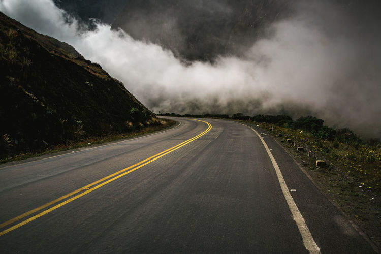 Country road against mountains in foggy weather