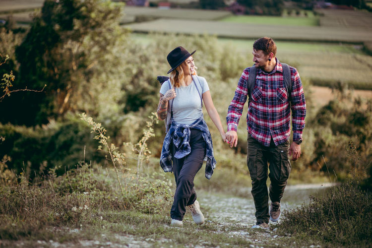 Full length of smiling young couple hiking on field