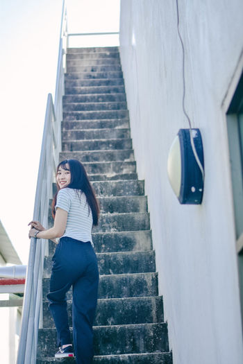 Full length of young woman climbing stairs while holding railing at building terrace