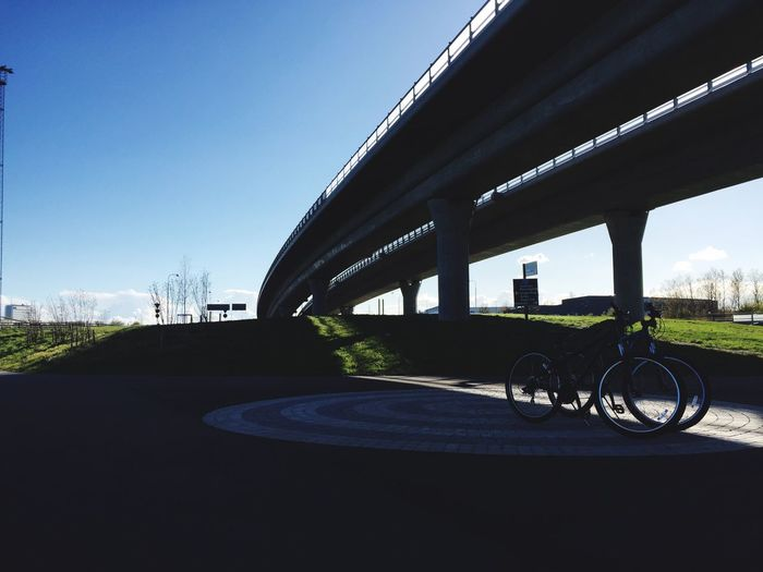 Bicycle parked by road against clear sky