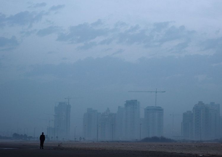 Man standing on street by buildings against cloudy sky in foggy weather