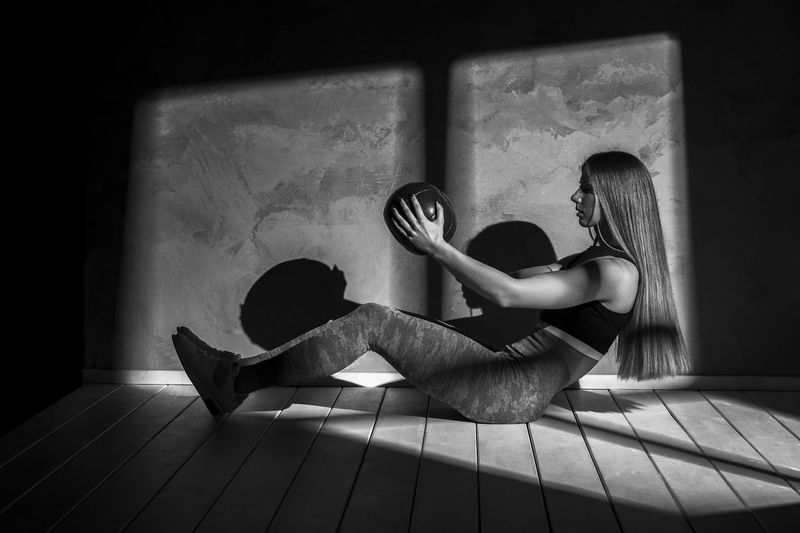 Woman exercising with equipment on floor against wall