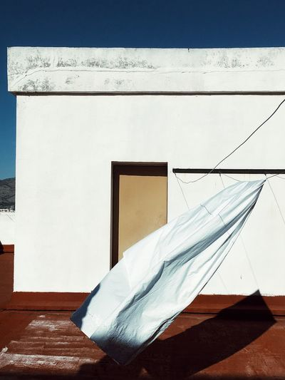 White textile hanging against built structure