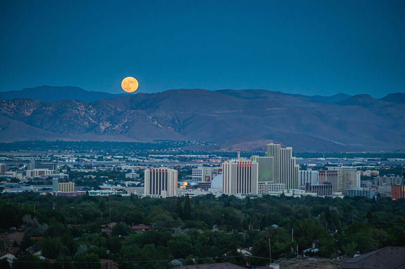 A bright full moon rises above the reno, nv skyline.