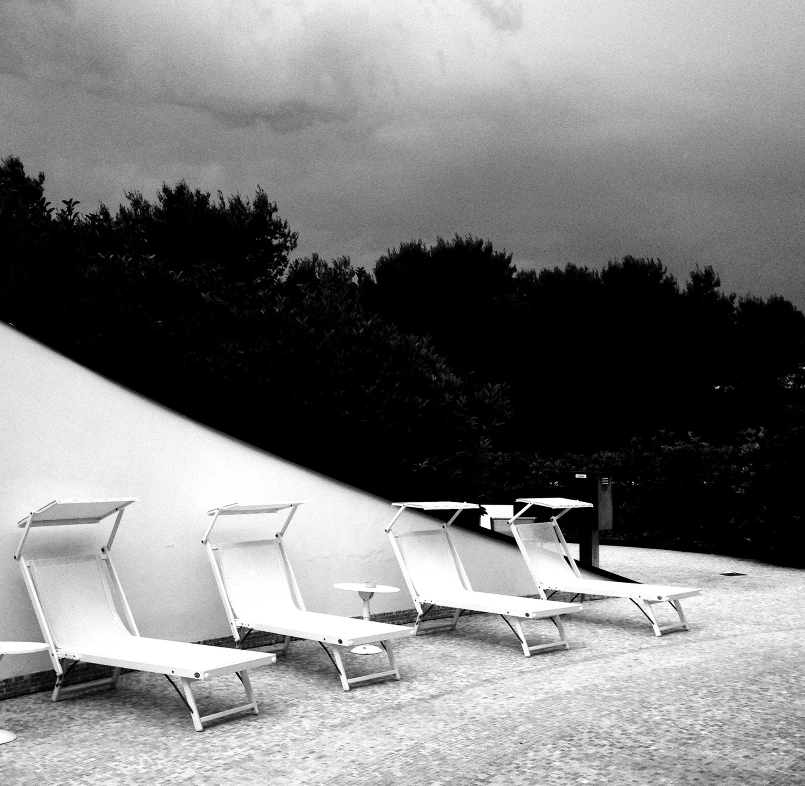 empty, chair, tree, sky, absence, seat, tranquility, tranquil scene, bench, nature, in a row, outdoors, day, no people, table, beach, cloud - sky, relaxation, scenics, shadow