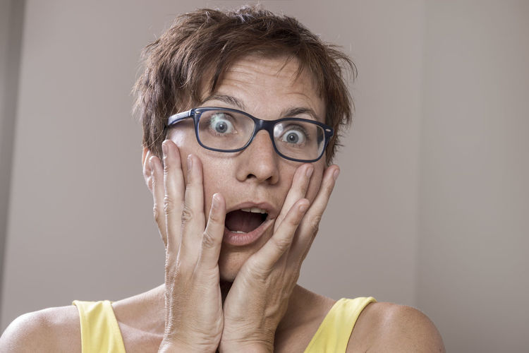 Close-up portrait of shocked woman at home