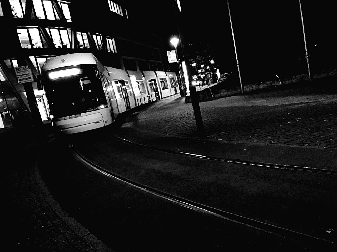 transportation, night, illuminated, public transportation, mode of transport, built structure, building exterior, architecture, railroad track, rail transportation, road, outdoors, land vehicle, city, no people