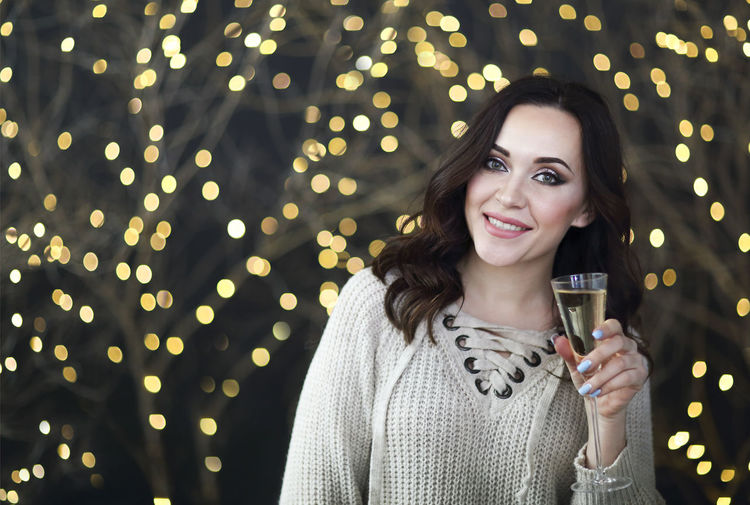 Portrait of smiling woman holding champagne against illuminated lights at night
