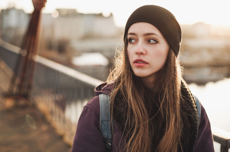 Young woman walking on the bridge Worried Beautiful Woman Contemplation Day Focus On Foreground Front View Leisure Activity Lifestyles Long Hair Looking One Person Outdoors Portrait Real People Susnset Teenager Walking Warm Clothing Young Adult Young Women