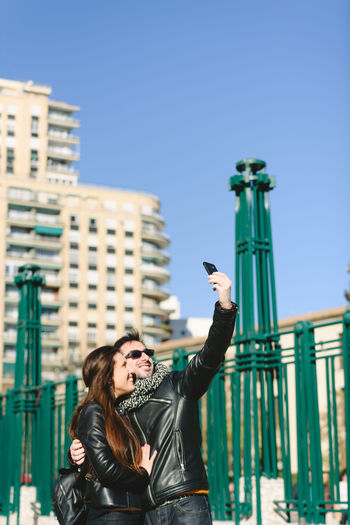 Portrait of young woman using mobile phone against sky