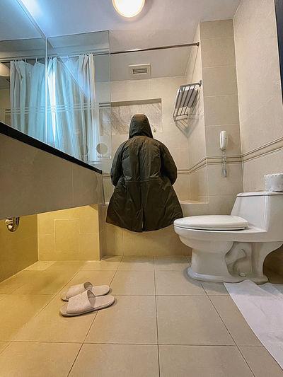 Rear view of man sitting in bathroom