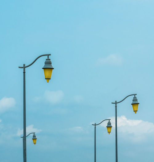 The street lamps under the clouds Lighting Equipment Street Light Street Sky Low Angle View Light Electric Light No People Blue Nature Day Outdoors Electricity  Cloud - Sky Copy Space Technology Pole Illuminated Yellow Electric Lamp Electrical Equipment