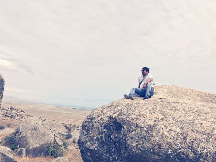 Man sitting on rock against cloudy sky