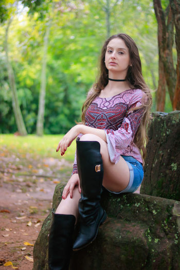 Casual Clothing Childhood Day Focus On Foreground Full Length Girls Leisure Activity Lifestyles Nature One Person Outdoors People Portrait Real People Sitting Tree Young Adult Young Women