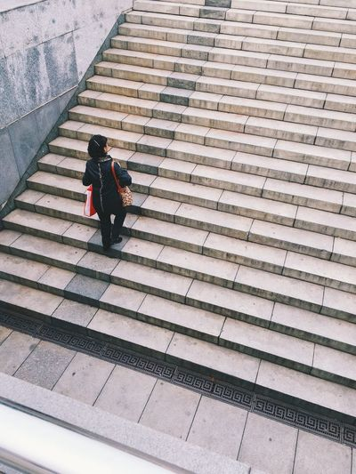 High angle view woman moving up on staircase