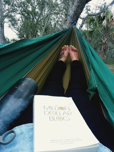 Low section of woman with book relaxing in hammock