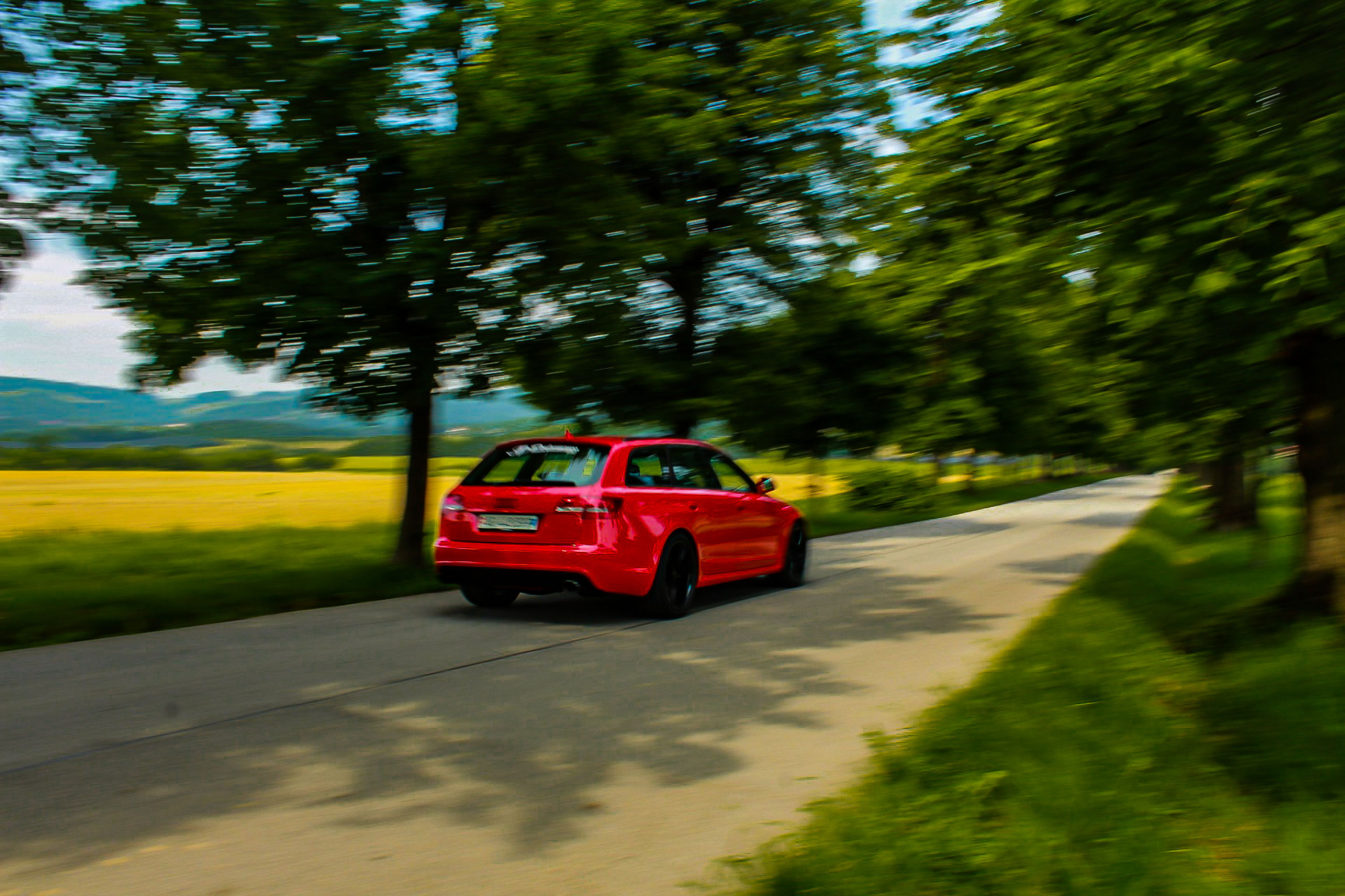 transportation, mode of transportation, tree, road, plant, land vehicle, motor vehicle, car, motion, nature, red, green color, blurred motion, no people, day, on the move, travel, city, sunlight, selective focus, outdoors, road trip