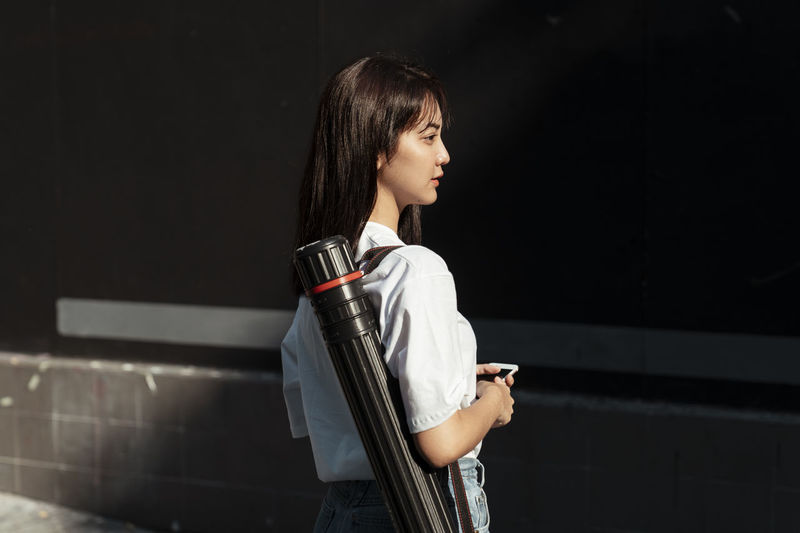 Side view of young woman using phone while standing against wall